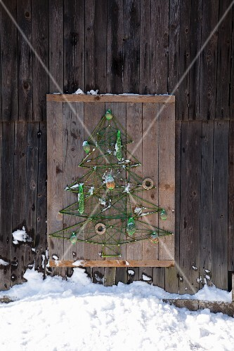 DIY bird-feeding station shaped like Christmas tree made from green cord on rustic wooden panel