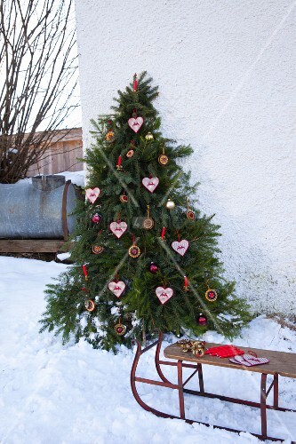 Christmas tree decorated with candles and home-made gingerbread shapes in snow