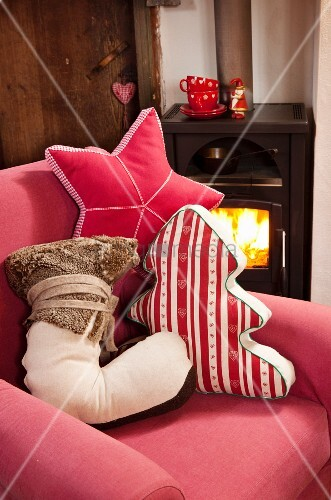 Hand-made, festive scatter cushions in the shapes of a tree, star and boot on red armchair