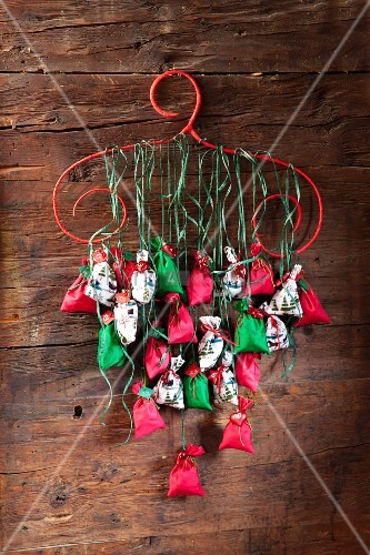 Advent calendar hand-made from numbered bags hung from red coathanger