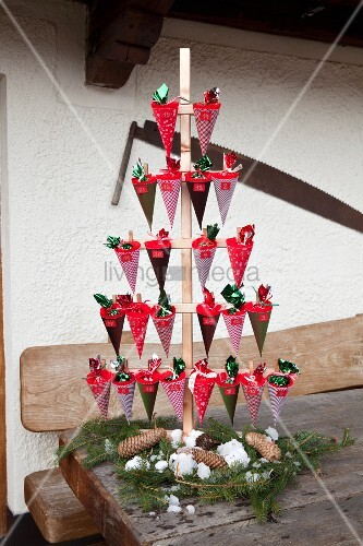 Hand-made Advent calendar with numbered cones in wooden stand on rustic wooden table