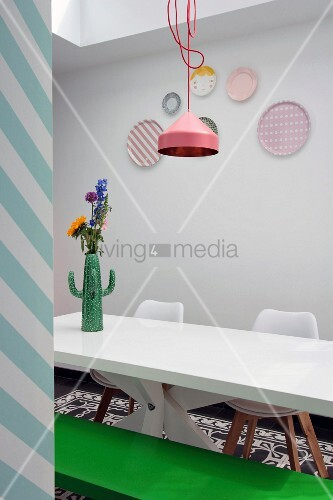 Cactus-shaped vase of flowers on white table in front of pastel decorative wall plates
