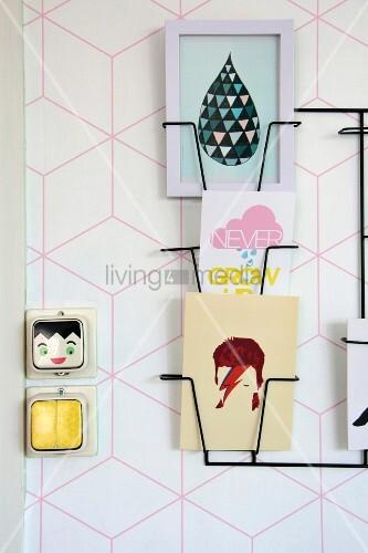 Schwarzer, filigraner Zeitungshalter an Wand mit geometrischem rosafarbenem Muster