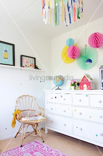 Cane chair, white chest of drawers and colourful paper pompoms in girl's bedroom