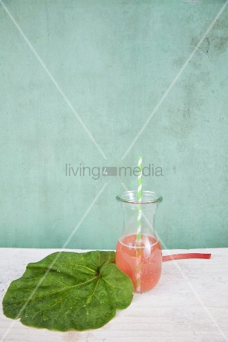 Drinking straw in carafe of rhubarb juice next to wrapped in rhubarb leaf