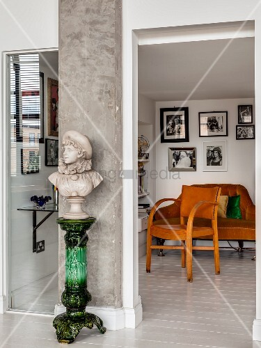 Bust on green plinth against concrete pillar in front of vintage armchair and sofa in reading area
