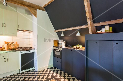 White, rustic fitted cupboards opposite modern dark cabinets against black wall in corner of kitchen