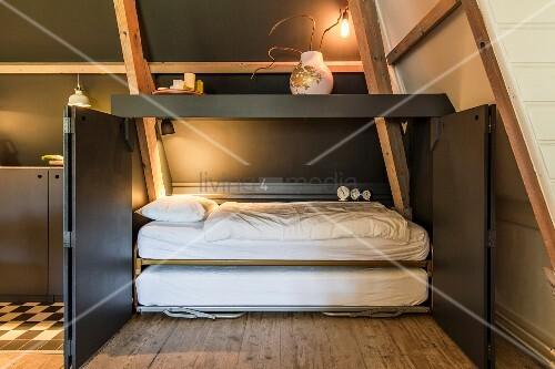 Fold-away bed in dark grey cupboard with open doors