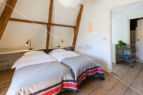 Twin beds with grey and red bedspreads under sloping ceiling with table lamps on lamp integrated into exposed roof structure