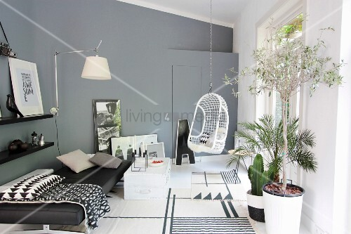 Couch, hanging chair, wall lamp and plants in modern living room in shades of grey