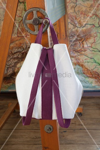 Hand-sewn backpack made from white knitted wool with purple straps hanging from blackboard crank handle