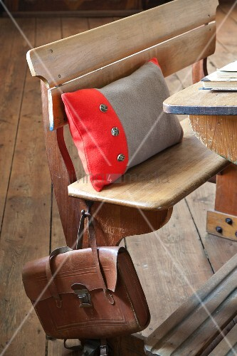Scatter cushion with two-tone boiled-wool cover on vintage school bench with old-fashioned leather satchel hanging from backrest