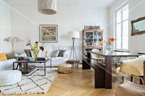Woollen rug and oak parquet flooring in open-plan living area of period apartment