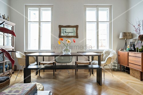Wooden table, various chairs, display cabinet and sideboard in period apartment