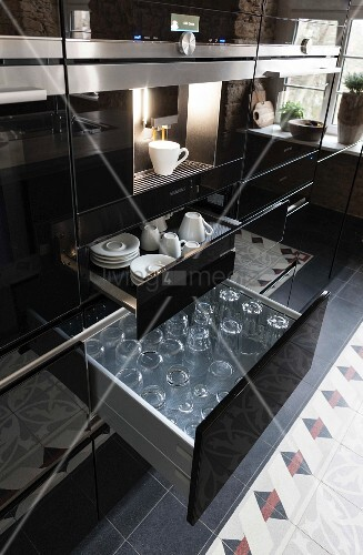 A kitchen cupboard with a shiny black surface, a coffee machine above an open drawer of cups and glasses