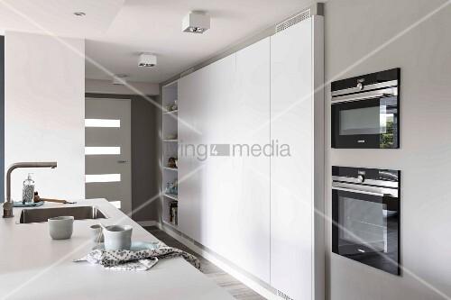 Ausschnitt einer Küchentheke, gegenüber moderner Einbauküchenschrank ...