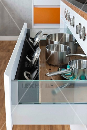An open drawer of pots and lids with a lid insert
