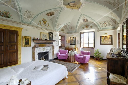 Pink armchairs in bedroom of elegant old villa with painted frescoes