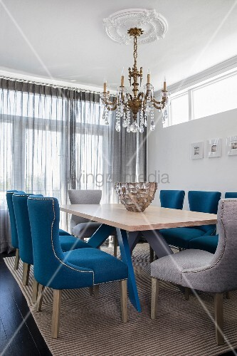 Upholstered chairs and chandelier in classic dining room