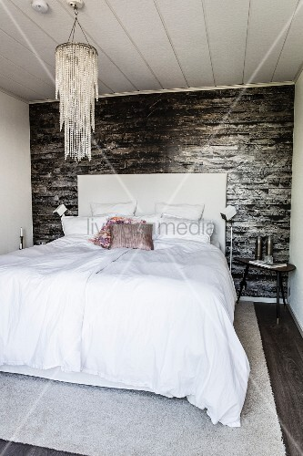 Double bed and chandelier in bedroom with dark wallpaper
