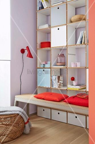 Raumhohes Regal mit pastellfarbenen Klappen, offenen Fächern und Schubladen, davor Sitzbank mit roten Kissen