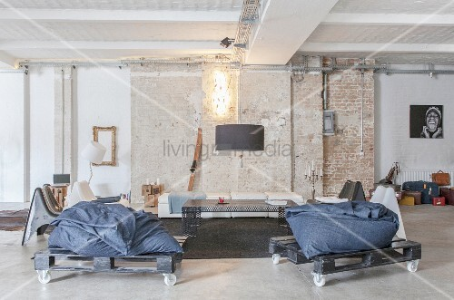 Beanbags on pallets on castors in lounge of loft apartment with brick wall and concrete floor