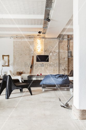 Lounge in industrial-style loft apartment with brick wall and concrete floor