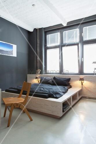 Doppelbett mit Stauraumlösung vor Fenster im Schlafzimmer