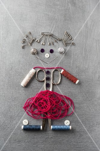 Sewing utensils arranged in shaper of a smiling girl