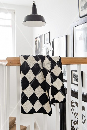 A hand-knitted black and white checked blanket made of Merino yarn