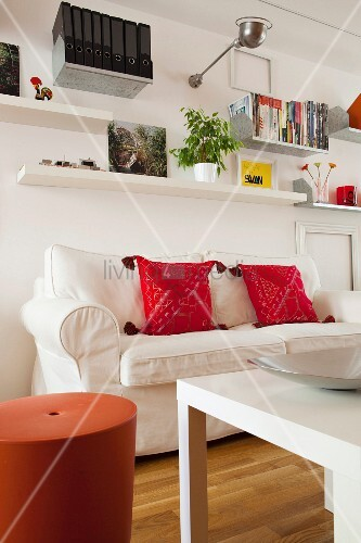 Red cushions on white loose-covered sofa below wall-mounted shelves