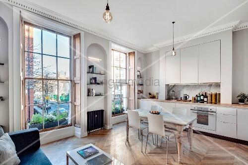 Offener Wohnraum mit Einbauküche, Esstisch und Sofa in renovierter Stadtwohnung