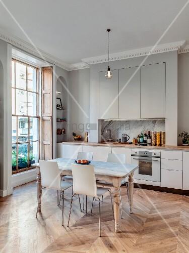 Esstisch mit Stühlen vor Einbauküche in renovierter Stadtwohnung