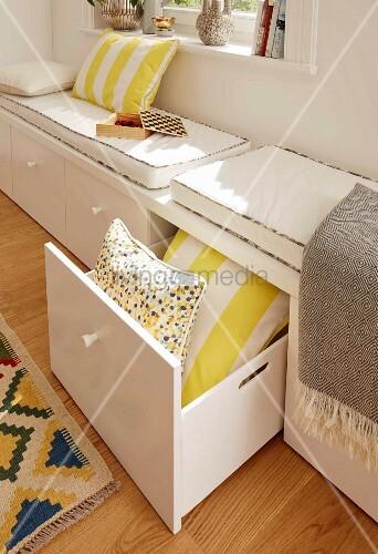Maßgefertigte Sitzbank mit Schubladen, Kissen und Sitzauflagen vor Fenster