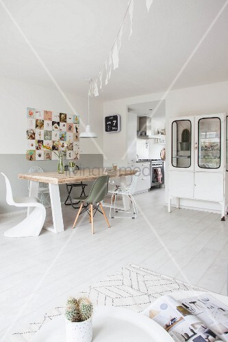 Dining table with rustic wooden top and various classic chairs below retro picture on wall and glass-fronted cabinet next to doorway leading to kitchen