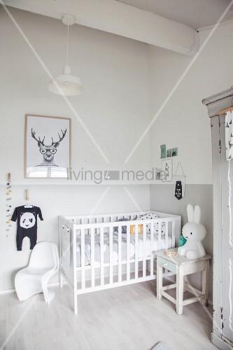 Gitterbett, Hocker mit Hasenfigur und Klassiker-Kinderstuhl in heller Zimmerecke