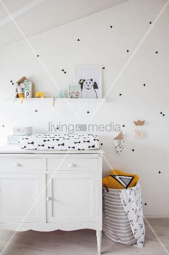 weiße Kommode mit Wickelauflage vor weisser Wand mit schwarzen Stickern