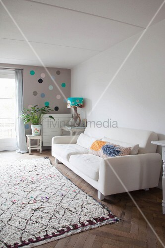 Scatter cushions in white sofa, houseplant on wooden stool and artistic table lamp