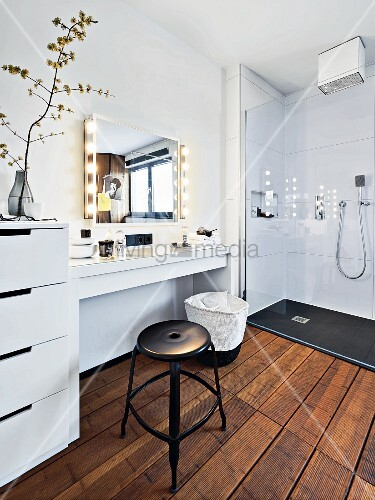 A modern white bathroom with a make-up table and a shower area with a glass panel