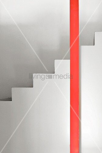 Round red column in front of white stairs