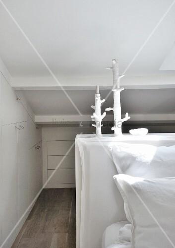 Platzsparende Einbauschränke Unter Dachschräge In Weißem Schlafzimmer Mit  Künstlerischen Kerzenständern
