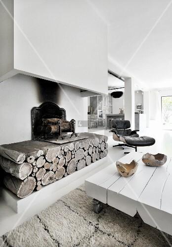 Weißer Bodentisch vor rustikaler Feuerstelle mit Kaminabzug
