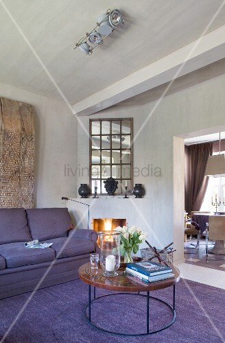 Open fire, mirror and round coffee table in purple lounge area