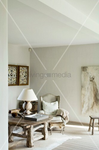 Rustikaler Massivholztisch auf Tierfellteppich neben antikem Ohrensessel und Gemälde