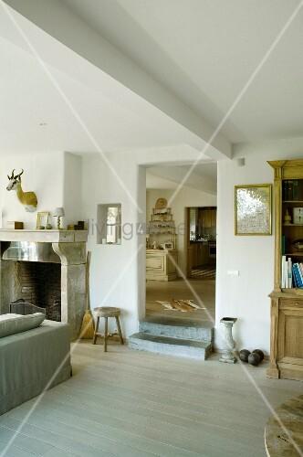 Wohnbereich mit offenem Kamin, und Dielenboden in renoviertem Landhaus