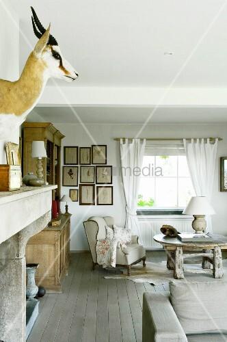 Ländlicher Wohnbereich mit Tiertrophäe und gemütlichem Ohrensessel