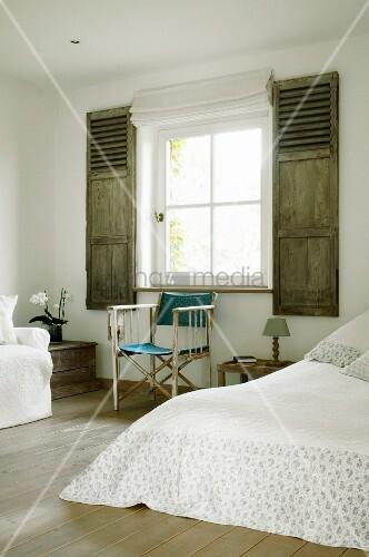 Director's chair on wooden floor in rustic bedroom with interior shutters