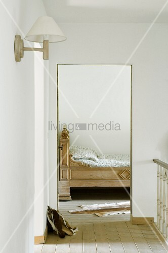 View from stairwell of ornate wooden bed and animal-skin rug