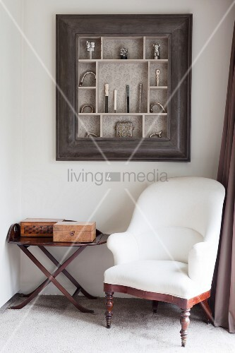 White antique armchair and side table below collection of walking-stick handles in display case