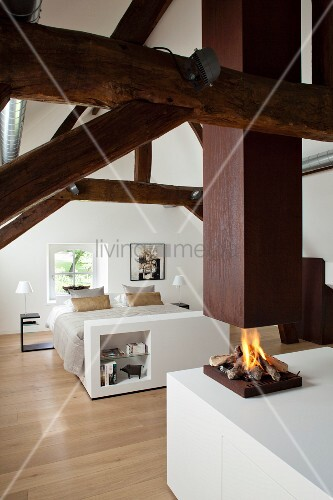 Elegantes weißes Dachgeschoss-Schlafzimmer mit restaurierter Fachwerkkonstruktion und offener Feuerstelle unter Kaminabzug